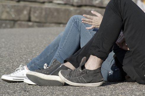 Couple enlacé - main tendue - allongés dans la rue
