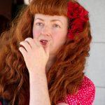 Portrait - Jolie femme rousse - Robe rouge - Fleurs rouges dans les cheveux